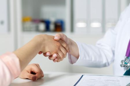 etica: Mujeres médico estrechar la mano con el paciente. Asociación, la confianza y la ética médica concepto. Apretón de manos con el cliente satisfecho. Apretón de manos Agradecido por tratamiento excelente. Foto de archivo