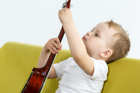 Little child sitting on couch and tuning ukulele guitar. Young talented kid holding small four stringed guitar. Musical instrument learning Stock Photo