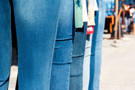 emporium: Row of mannequins with different coloured jeans on market. Some outwear examples in a line before shop. Clothes sale concept. Pants on dummies.