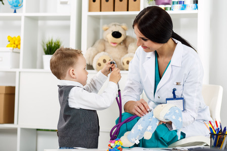 paediatrics: Family doctor examination. Little child visiting pediatrician playing with stethoscope. Beautiful female medical freckled doctor  communicating with cute young patient. Paediatrics medical concept Stock Photo