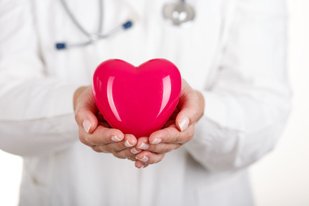 Female doctorss hands holding and covering red toy heart. Doctors hands closeup. Medical help, prophylaxis or insurance concept. Cardiology care,health, protection and prevention.
