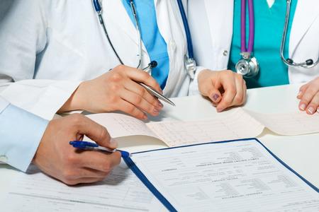 환자의 심전도 차트를 검사 세 가지 의학 의사 손. 전문 대화, 심장병 전문의의 의회. 동료의 회의를 작동합니다. 심장 질환 치료의 의료 상담 개념