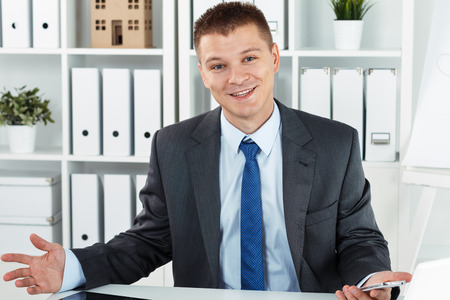 cordiality: Funny friendly smiling businessman in suit at office working desk making helpless gesture. Joyful business man holding cellphone and making greeting gesture. Negotiations strategy concept