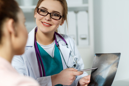 recommendations: Smiling medicine female doctor in glasses explains to patient diagnosis pointing with pen to x-ray picture. Patient listening carefully doctors recommendations. Medical concept. Radiologist or traumatologist