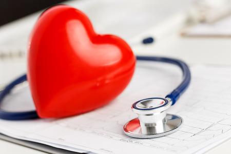 disease prevention: M�dico estetoscopio y el coraz�n del juguete rojo tirado en la carta de electrocardiograma de cerca. Ayuda m�dica, profilaxis, prevenci�n de enfermedades o concepto de seguro. Cuidado de Cardiolog�a, la salud, la protecci�n y la prevenci�n