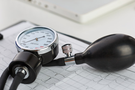 blood pressure bulb: Medical manometer lying on cardiogram chart closeup. Medical help, prophylaxis, disease prevention or insurance concept. Cardiology care,health, protection and prevention. Healthy life concept