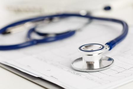 Estetoscopio médico que miente en diagrama electrocardiograma de cerca. Ayuda médica, profilaxis, prevención de enfermedades o concepto de seguro. Cuidado de Cardiología, la salud, la protección y la prevención. Concepto sano de la vida