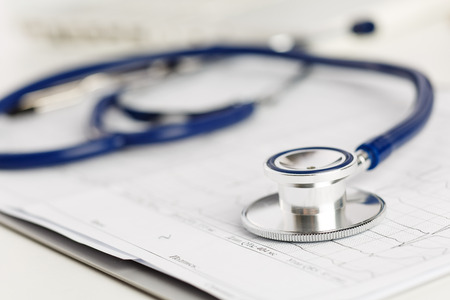 estetoscopio: Estetoscopio m�dico que miente en diagrama electrocardiograma de cerca. Ayuda m�dica, profilaxis, prevenci�n de enfermedades o concepto de seguro. Cuidado de Cardiolog�a, la salud, la protecci�n y la prevenci�n. Concepto sano de la vida Foto de archivo