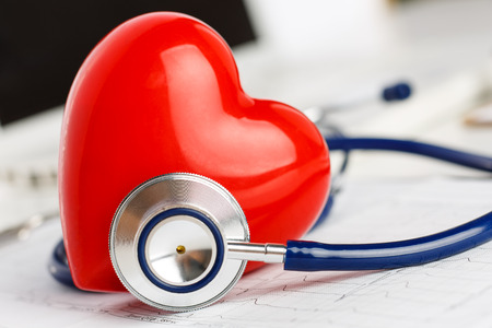 myocardium: Stetoscopio medico e cuore rosso giocattolo che si trova sul grafico cardiogramma primo piano. Assistenza medica, la profilassi, la prevenzione delle malattie o concetto di assicurazione. Assistenza cardiologia, salute, protezione e prevenzione