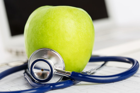 cure prevention: Green ripe fresh tasty apple lying on cardiogram chart surrounded with stethoscope. Medical help or insurance concept. Health life and wholesome food concept. Vegetarian lifestyle concept