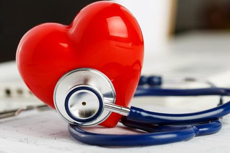 건강: 의료 청진 기 및 심전도 차트 근접 촬영에 누워 빨간색 장난감 심장입니다. 의료 지원, 예방, 질병 예방 또는 보험 개념입니다. 심장 치료, 건강, 보호 및 예방