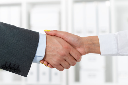 Male and female handshake in office. Businessman in suit shaking womans hand. Serious business and partnership concept. Partners made deal and sealed it with handclasp. Formal greeting gesture