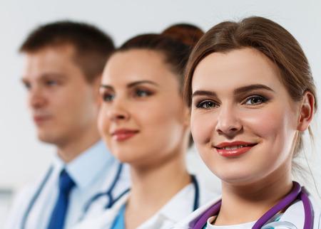 fila de personas: Tres m�dicos de medicina se enfrenta en la fila de cerca. Grupo de m�dicos con orgullo presenta y que mira en la c�mara sonriendo. Mejor equipo de profesionales de concepto. Retratos de tres m�dicos de pie uno por uno