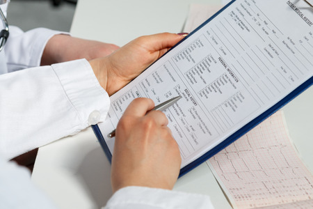 systole: Two female medicine doctors hands examining patient documents. Professional conversation, council of cardiologists. Working conference of colleagues. Medical concept of heart disease treatment Stock Photo