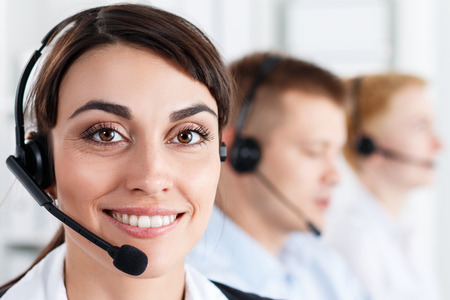 helpdesk: Three call center service operators at work. Portrait of smiling pretty female helpdesk employee with headset at workplace. Effective and efficient business information, help and support concept