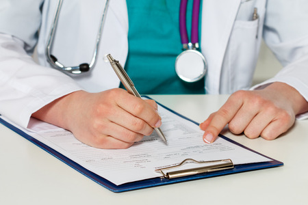 女性医学医師の手が患者の医療のフォームを充填します。病院事務室で紙を扱う医師。いくつかの書類を作る作業テーブルに座って治療学者。銀の