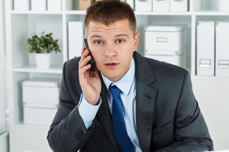 phone conversation: Surprised businessman in suit sitting at working table in office an talking cellphone. Bewildered man solving problem remotely by phone conversation. Sudden difficult situation concept