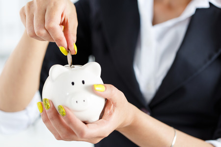 white piggy bank: Female hand putting pin money coins into white piggybank slot. Budgeting expenses concept. Making savings and effective investment concept. Future needs deposit