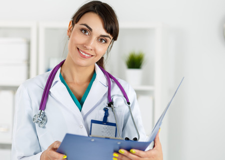 doctors tools: Beautiful female medicine doctors holding document folder portrait. Medical help or insurance concept. Friendly smiling therapeutist waiting for patient to examine. Physician reception concept Stock Photo