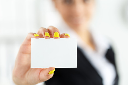Businesswoman in suit hand holding blank calling card. Female hand showing white visiting card in camera closeup. Partners contact information exchange concept. Introducing gesture at formal meeting