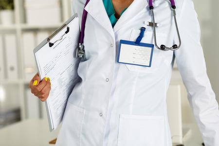 bata blanca: Médicos de medicina femenina que sostiene recortan documento almohadilla con el escudo en su primer pecho. Ayuda médica o concepto de seguro. El doctor está esperando paciente a examinar. Concepto de la recepción Médico Foto de archivo