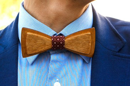 catchy: Fashionable wooden bow tie closeup. Retro style gentleman in blue woollen suit at wedding event Stock Photo