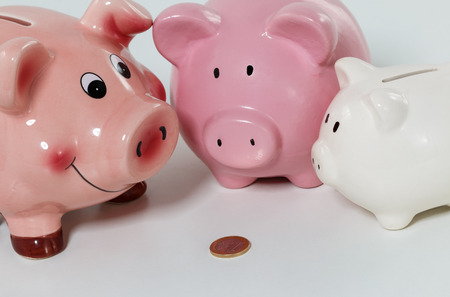 budget: Three piggybanks on table with a coin closeup. Budgeting expenses and sharing savings concept. Making savings and effective investment concept. Future needs deposit