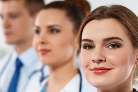 medics: Three medicine doctors faces in row closeup. Group of medics proudly posing and looking in camera smiling. Best team of professionals concept. Portraits of three medics standing one by one