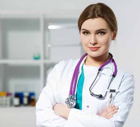 diagnosing: Beautiful female medicine doctor standing in her office with hands crossed on her chest. Medical help or insurance concept. Doctor is waiting for patient to examine. Physician reception concept