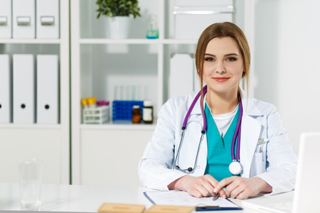 Beautiful young female therapist doctor sitting in front of working table smiling and looking in camera. Physician waiting for patient or listening carefully to him. Medical concept