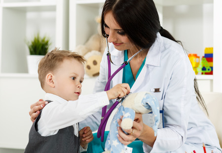 paediatrician: Family doctor examination. Little child visiting pediatrician playing with stethoscope. Beautiful female medical freckled doctor  communicating with cute young patient. Paediatrics medical concept Stock Photo