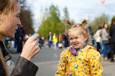 babysitter: Mother with daughter outdoor playing and making soap bubbles. Beautiful young smiling woman blowing bubbles to smiling little girl. Childhood and parenthood concept. Baby-sitter with kid Stock Photo