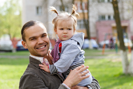 babysitter: Father with daughter outdoor looking in camera. Handsome young smiling dad  holding little girl with serious face. Childhood and parenthood concept. Baby-sitter with kid