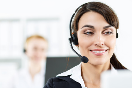 ear phone: Call center service operators at work. Portrait of smiling pretty female helpdesk employee with headset at workplace. Effective and efficient business information, help and support concept