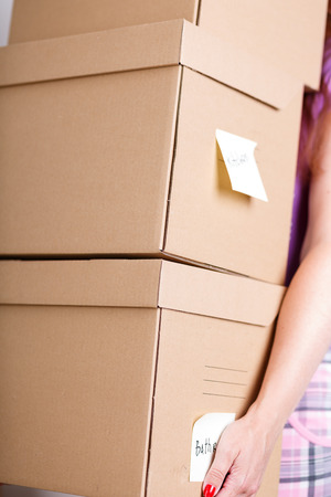 rearrangement: Female hand holding pile of brown cardboard boxes with house or office goods background. Moving to new place of living concept. Rearrangement, cleaning or reordering concept Stock Photo