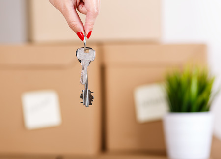 Female hand holding keys over pile of brown cardboard boxes with house or office goods background. Moving to new place of living concept.