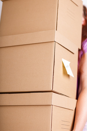 Female hand holding pile of brown cardboard boxes with house or office goods background. Moving to new place of living concept. Rearrangement, cleaning or reordering concept Stock Photo