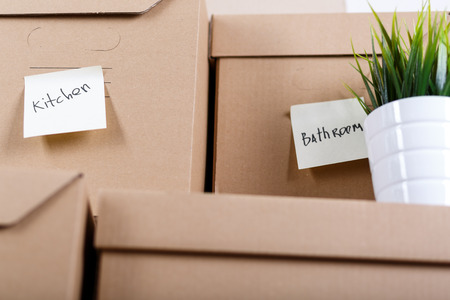 storeroom: Pile of brown cardboard boxes with house or office goods. Different stuff packed in carton boxes. Moving concept. Set of cargo boxes with yellow sticker labels ready for transportation and unpacking