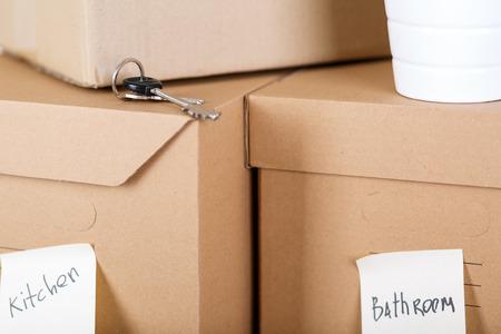 cajas de carton: Pila de cajas de cartón de color marrón con la casa o de la oficina de bienes. Cosas diferentes envasados ??en cajas de cartón. Concepto en movimiento. Conjunto de cajas de carga con etiqueta amarilla etiquetas listo para el transporte y desembalaje Foto de archivo