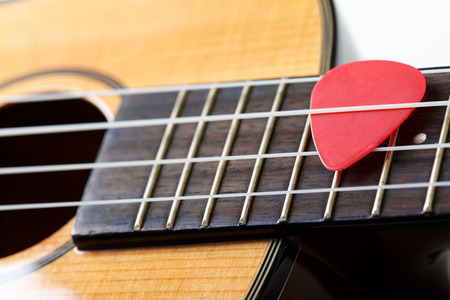 stringed: Small Hawaiian four stringed ukulele guitar with red pick between strings closeup. Musical instruments shop or learning school concept