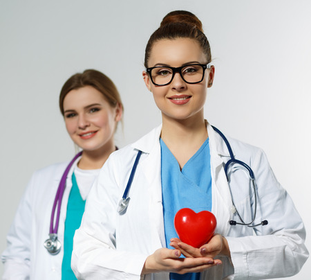 heart surgery: Beautiful smiling female doctor holding red heart in front of chest. Medical help, prophylaxis, insurance, surgery and resuscitation concept. Cardiology care,health, protection and prevention Stock Photo