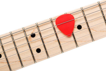 frets: Empty wooden maple fingerboard with red pick between strings of classic shaped electric guitar closeup isolated on white background with clipping path. Free frets and strings as improvisation concept Stock Photo