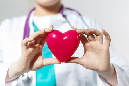 resuscitation: Female medicine doctor hands holding toy heart in front of chest closeup. Medical help, prophylaxis, insurance, surgery and resuscitation concept. Cardiology care, health, protection and prevention Stock Photo