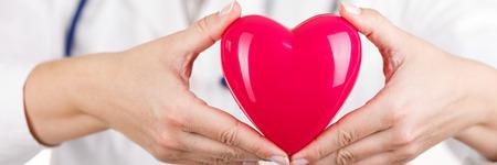 醫療保健: 女醫學博士的手中拿著紅色的玩具心臟在她的胸部特寫鏡頭面前。信箱觀點。醫療幫助,預防或保險的概念。心內科護理,健康,保護和預防