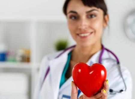 myocardium: Bella sorridente medico femminile che tiene cuore rosso in primo piano davanti al petto. Assistenza medica, la profilassi, l'assicurazione, la chirurgia e il concetto di rianimazione. Assistenza cardiologia, salute, protezione e prevenzione