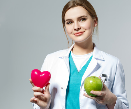 health concern: Beautiful smiling female doctor holding red heart and green apple in front of chest. Health life and wholesome food concept. Vegetarian lifestyle concept. Cardiology concept