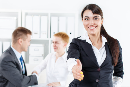 welcome people: Beautiful smiling business woman in suit offering hand to shake while couple employees working in background. Serious business and partnership concept. Formal greeting and welcoming gesture
