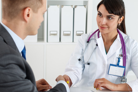 handclasp: Beautiful smiling female medicine doctor shaking hands with male patient. Partnership, trust and medical ethics concept. Handshake with satisfied client. Thankful handclasp for excellent treatment Stock Photo