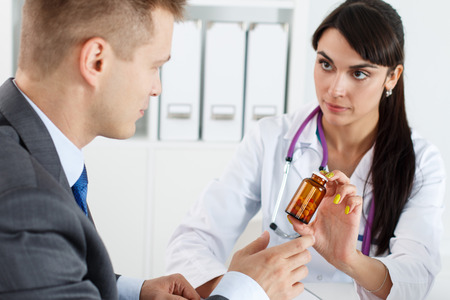 sexual health: Beautiful female medicine doctor giving to male patient in business suit jar of pills. Antidepressant or man sexual potency cure. Medical and pharmacy concept. Businessman visiting therapeutist