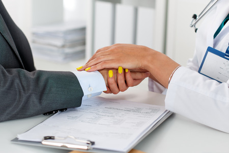 bad news: Friendly female doctors hands holding male patients hand for encouragement and empathy. Partnership, trust and medical ethics concept. Bad news lessening and support. Patient cheering and support